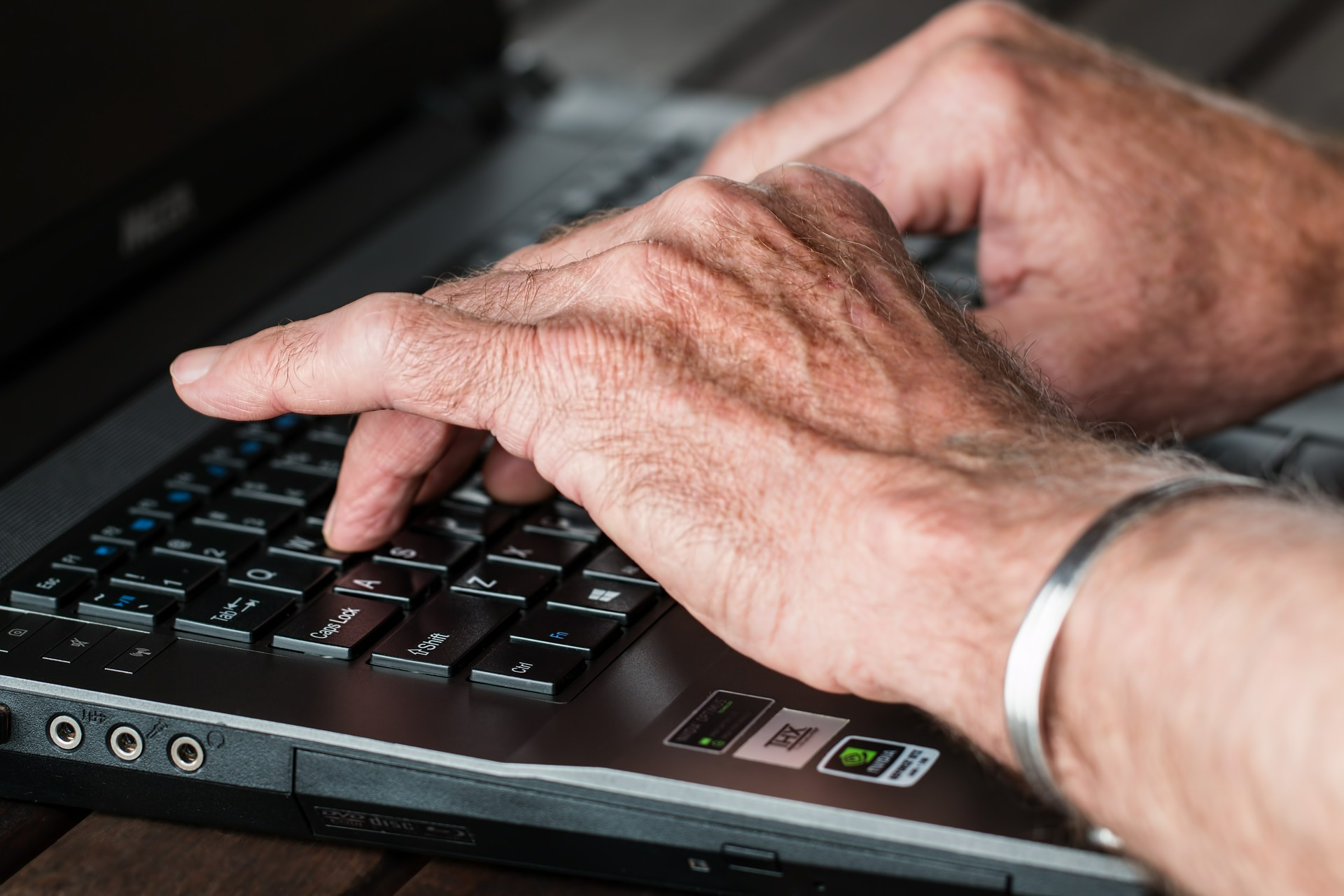 Arthritic hands typing on laptop keyboard